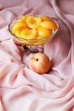 在糖浆和玻璃花瓶的桃子 免版税库存照片