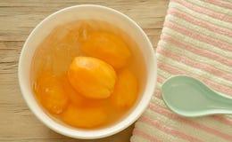 在糖浆的李子芒果热带水果用在杯子的冰冷的点心 免版税库存图片
