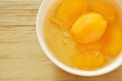 在糖浆的李子芒果热带水果用在杯子的冰冷的点心 库存照片