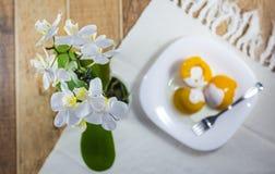在糖浆的桃子用奶油色牛奶,点心在用花瓶装饰的桌上的一个白色盘服务兰花 免版税图库摄影