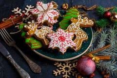 在糖釉的可口甜圣诞节姜饼在一个欢乐桌集合 免版税库存照片