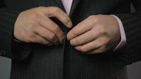 在紧固在夹克,样式,特写镜头的黑衣服的商人上部按钮 股票录像