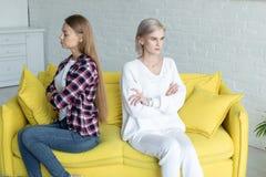 在紧接坐用crosed手的便服的女同性恋的女性夫妇在黄色沙发在争吵以后 库存照片