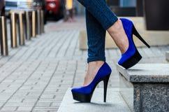 在紧的牛仔裤和蓝色天鹅绒hig的美好的苗条女性腿 免版税图库摄影