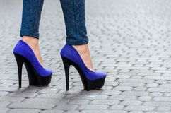 在紧的牛仔裤和蓝色鞋子的美好的苗条女性腿在a 库存图片