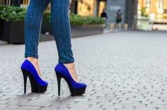 在紧的牛仔裤和蓝色鞋子的美好的苗条女性腿在a 图库摄影