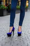 在紧的牛仔裤和蓝色鞋子的美好的苗条女性腿在a 免版税库存图片