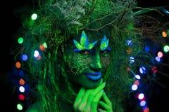 在紫外流体黑光的神秘的绿色树精与在背景的发光的树 免版税库存图片