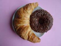 在紫罗兰色背景的美味的新月形面包和巧克力多福饼 顶视图 库存图片
