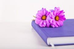 在紫罗兰色闭合的笔记本的两朵紫色菊花花在白色木背景 免版税库存图片