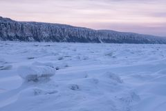 在紫色口气的冬天风景与在冻河的山脊冰日落的 免版税库存图片