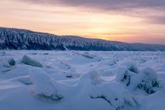 在紫色口气的冬天风景与在冻河的山脊冰 免版税库存图片