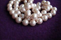 在紫色开士米背景堆的珍珠项链 库存图片