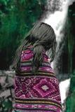 在紫色毯子的美丽的亚洲女孩画象在美丽的自然瀑布和绿色森林前面 免版税库存照片