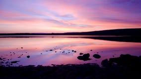 在紫色海运日落水 免版税库存图片