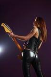 在紫色背景的性感的吉他演奏员 库存照片