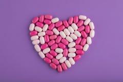 在紫色背景的糖果心脏 库存照片