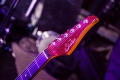 在紫色音乐会光的洋红色吉他fretboard 免版税图库摄影