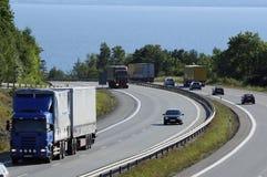 在繁忙的高速公路的卡车和业务量 图库摄影