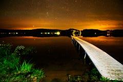在繁星之夜日落下的湖 图库摄影
