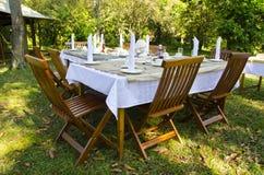 在繁茂花园里布置的餐桌 免版税库存图片
