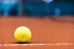在红土网球场的网球 库存照片