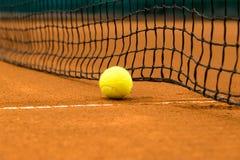 在红土网球场的网球 免版税库存图片