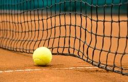 在红土网球场的网球 免版税库存照片