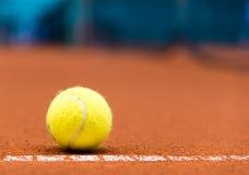 在红土网球场的网球 图库摄影