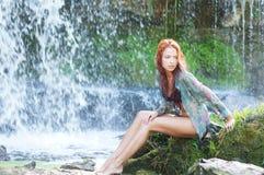 在红头发人坐的瀑布妇女年轻人附近 库存照片