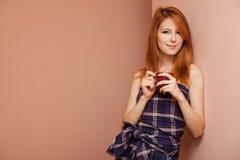 在红头发人墙壁附近的美丽的女孩 库存图片