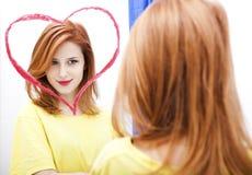 在红头发人附近的女孩镜子 免版税库存图片