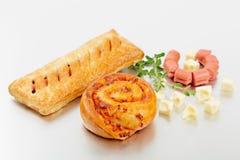 在红润酵母小圆面包的香肠与被隔绝的一个金黄外壳 免版税库存图片