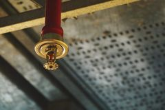 在红潮管道系统的自动天花板火喷水隆头 免版税库存图片