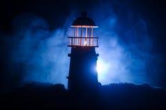 在红火背景后的可怕黑暗的不祥的灯塔 在黄昏日落灯塔灯塔的灯塔日落的 Decorat 免版税库存照片