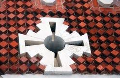 在红砖墙壁上的白色十字架 库存图片