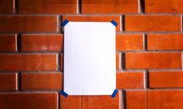 在红砖墙壁上的白色板料a4 库存图片