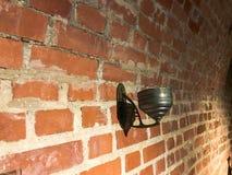 在红砖墙壁上的老古色古香的金属灯持有人 库存图片
