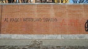 在红砖墙壁上的街道画在意大利说法Al fasci nessuno spazio,被翻译为法西斯主义者的没有室- antifa题材 库存图片