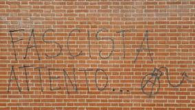 在红砖墙壁上的街道画在意大利说法Fascisti Attento用炸弹和A,被翻译为法西斯主义者威胁观看外 库存照片
