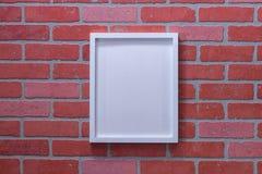 在红砖墙壁关闭画象的白色画框 库存图片
