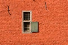 在红砖墙壁的两个小窗口 免版税库存照片