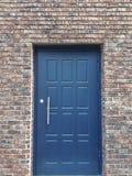 在红砖墙壁的蓝色金属门 免版税库存照片