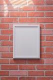在红砖墙壁画象的白色画框 免版税库存图片
