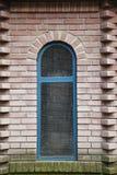 在红砖大厦的蓝色窗口 免版税库存照片