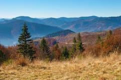 在红色、桔子和yello报道的发烟性山脉的小山 免版税图库摄影