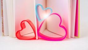 在红色丁香和蓝色上色的树心脏在一本开放日志预定与从书出来的好的火光 库存照片