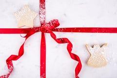 在红色丝带包裹的大理石酥皮点心板的天使和星脆饼拂去了灰尘用糖果商糖 库存照片