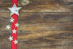 在红色丝带的圣诞节星 圣诞节的欢乐背景 免版税库存照片