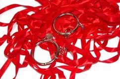 在红色丝带的钢手铐 图库摄影